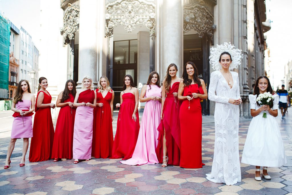 Image depicts a bride in custom gown with her bridal party