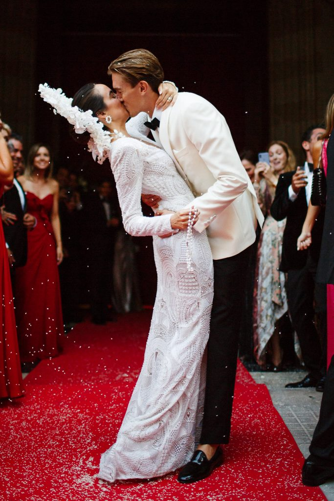 Image depicts a bride and groom embraced in a kiss, standing on red carpet surrounded by their wedding party