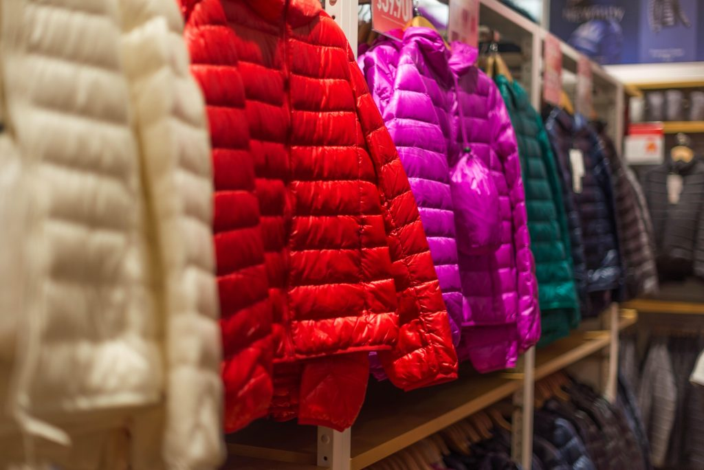 Row of puffy winter coats hanging in a store display